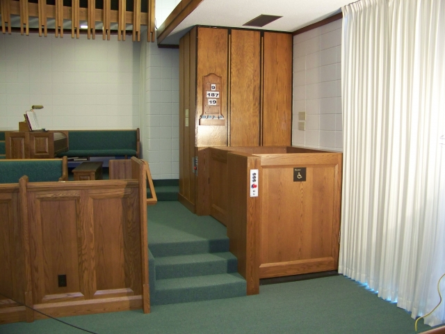 Both lift doors are closed. Lift in church provides access to and from the chancel. Lift encased in wood millwork blending in with surrounding aesthetics. Lift function readily available, independently operable.