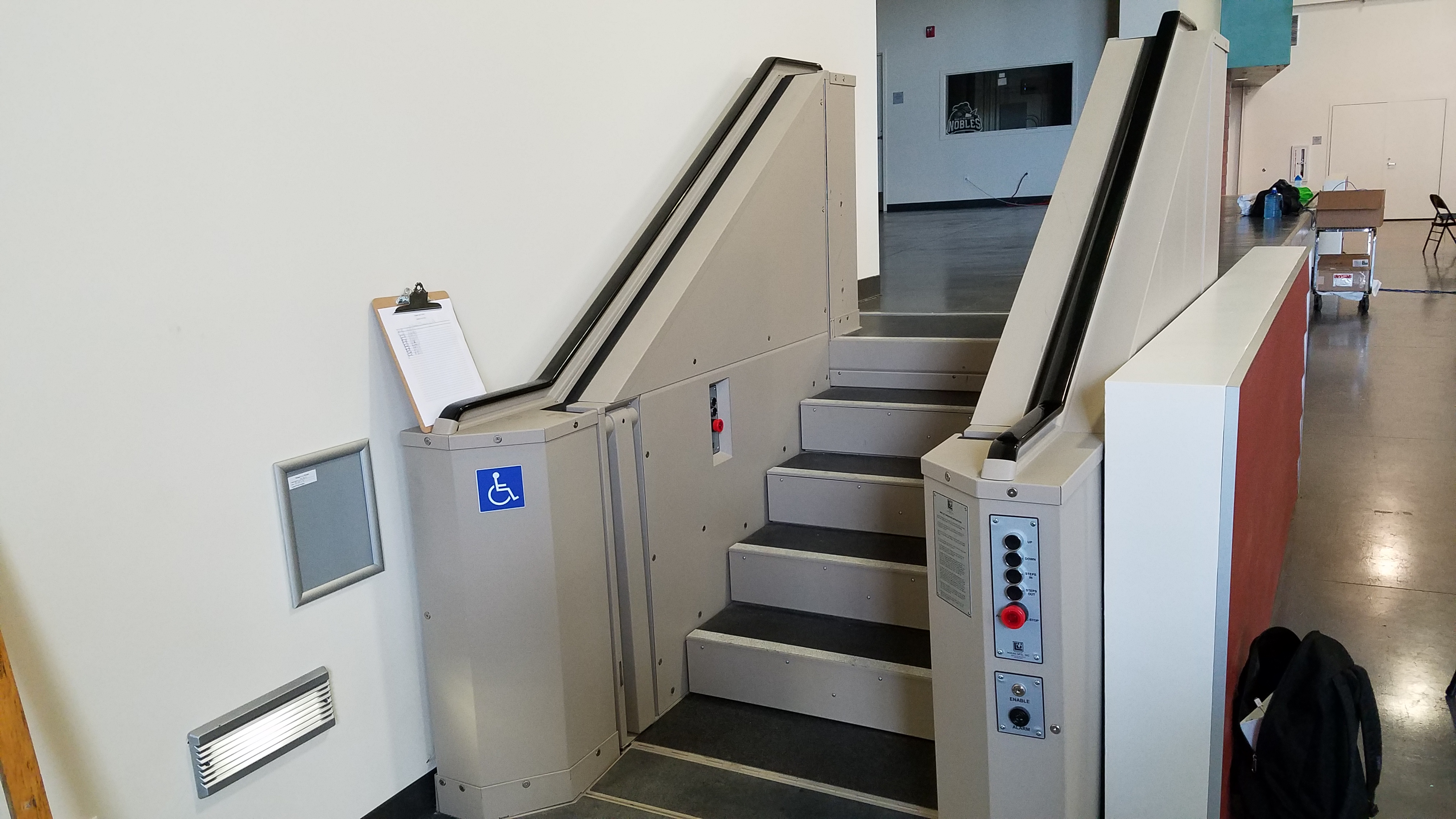 Tan in color. In step position for ambulatory access to stage. Lift function readily available, independently operable.