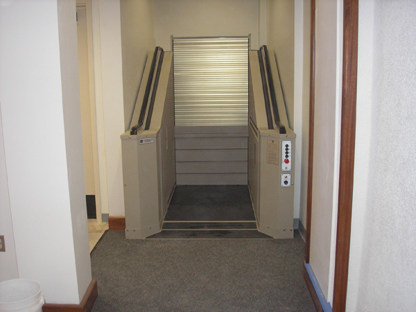 Tan in color. Steps are retracted. The lift is ready to accept a passenger to run the lift to the upper level to exit the boardroom.