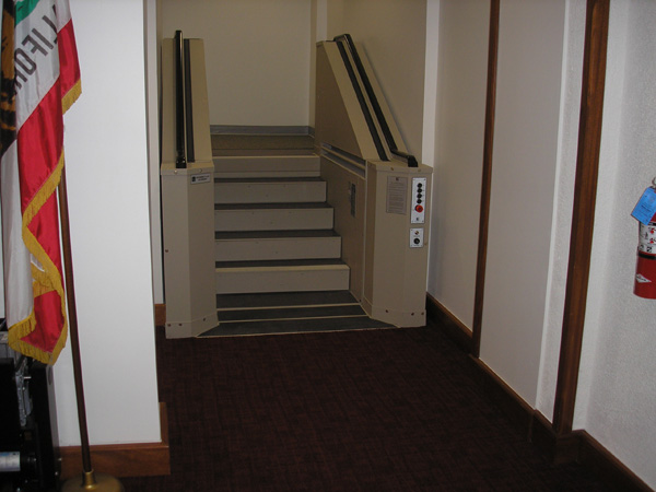 Tan in color. In step position for ambulatory access to boardroom. Lift function readily available, independently operable.