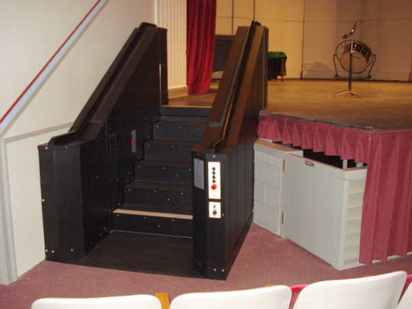 Black in color. In step position for ambulatory access to stage in auditorium. Lift function readily available, independently operable.