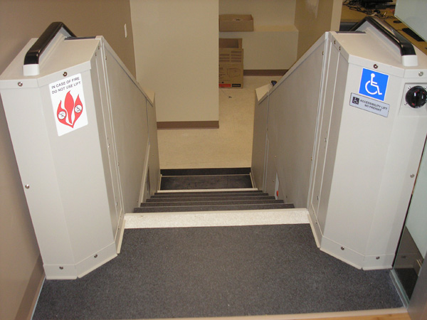 Tan in color. View from upper level looking down the steps into imaging room. Lift function readily available, independently operable.
