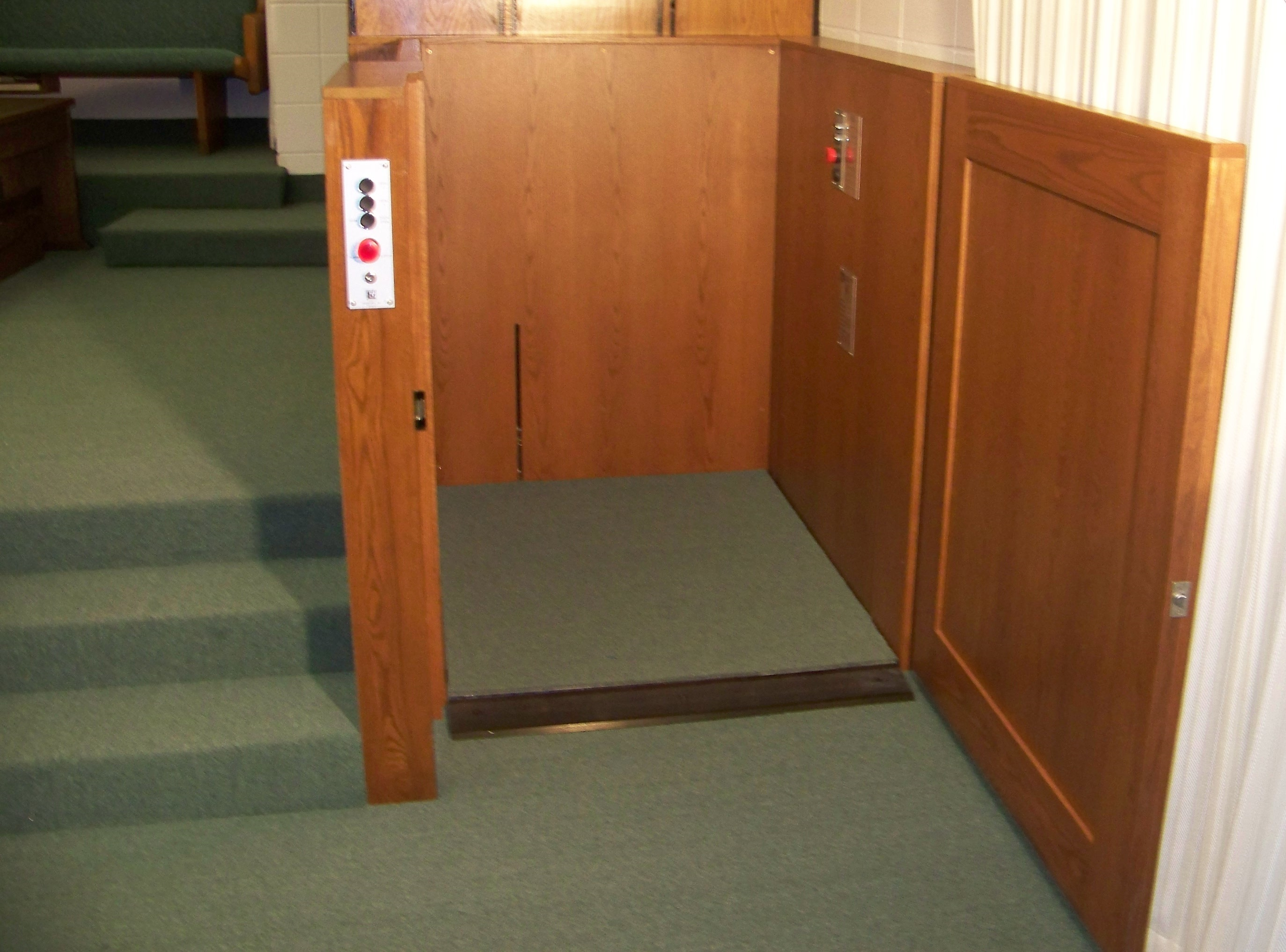 Lift door at lower level is opened. Lift in church provides access to and from the chancel. Lift is positioned next to stairs and is encased in wood millwork blending in with surrounding aesthetics. Lift function readily available, independently operable.