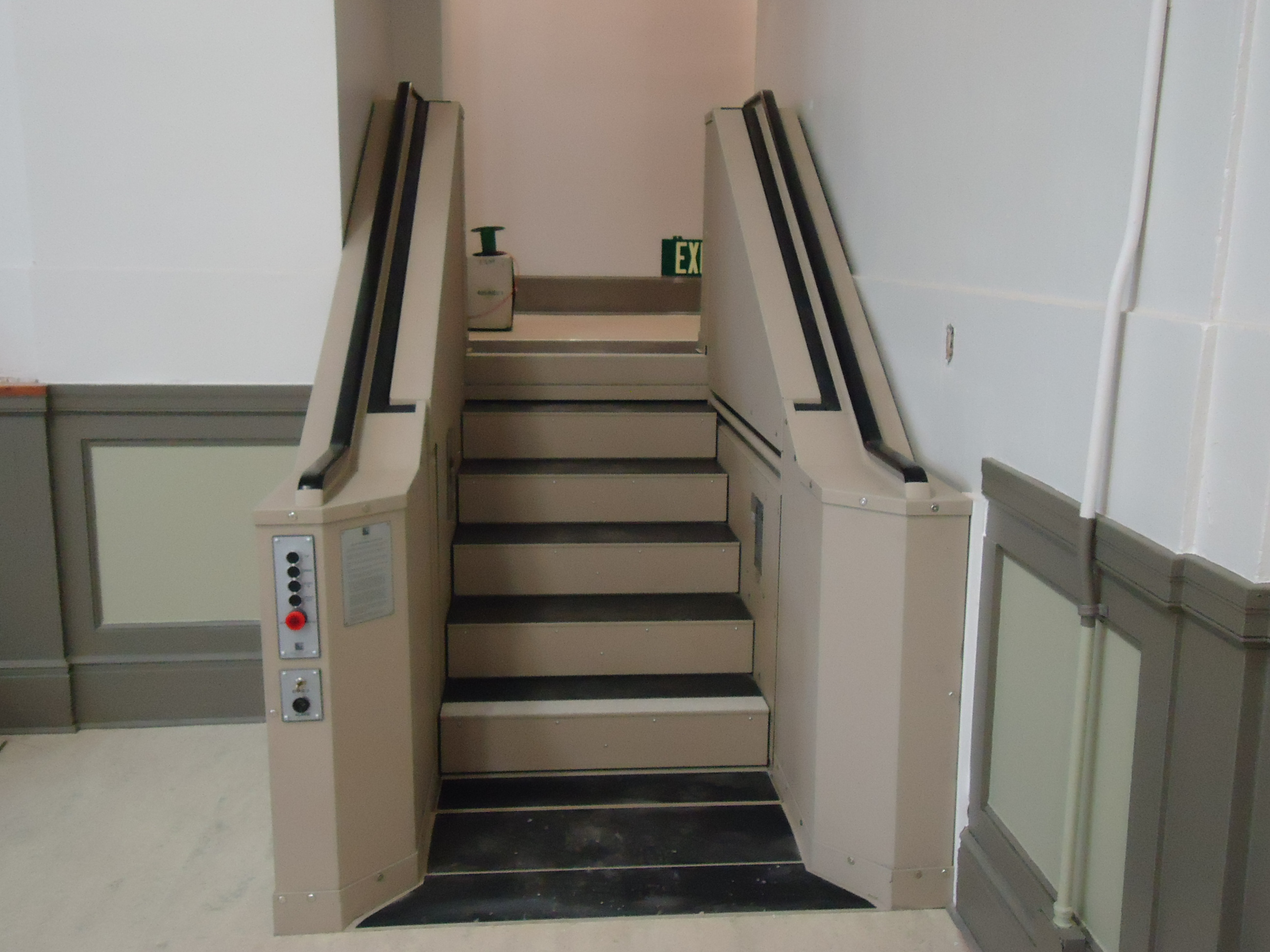 Tan in color. In step position for ambulatory access to stage in a school multipurpose room. Lift function readily available, independently operable.