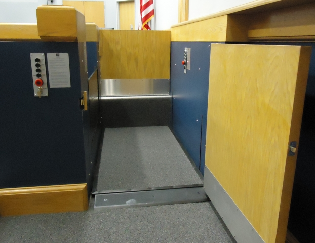 Witness lift positioned at lower level with lower level door opened and the door to the judge's bench closed. Equipped with threshold ramp to allow wheelchair access. Lift encased in wood millwork blending in with courtroom millwork. Lift is readily available and independently operable.
