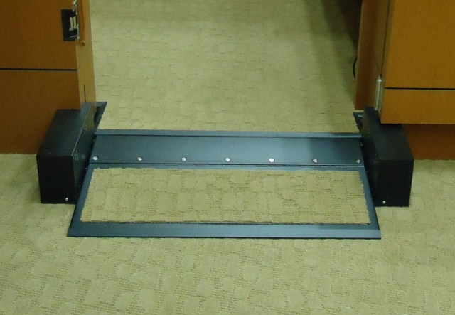 Close-up view of operable step in the ramp position.