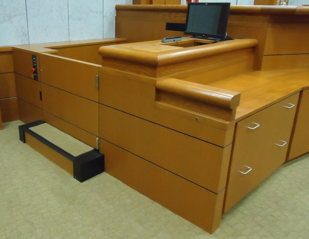 Witness lift positioned at witness level with lower level door closed. Equipped with operable step to allow ambulatory access. Lift encased in wood millwork blending in with courtroom millwork. Lift is readily available and independently operable.