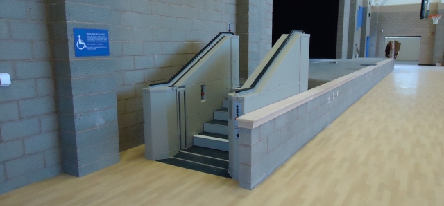 Tan in color. In step position for ambulatory access to stage in gymnasium. Lift function readily available, independently operable.