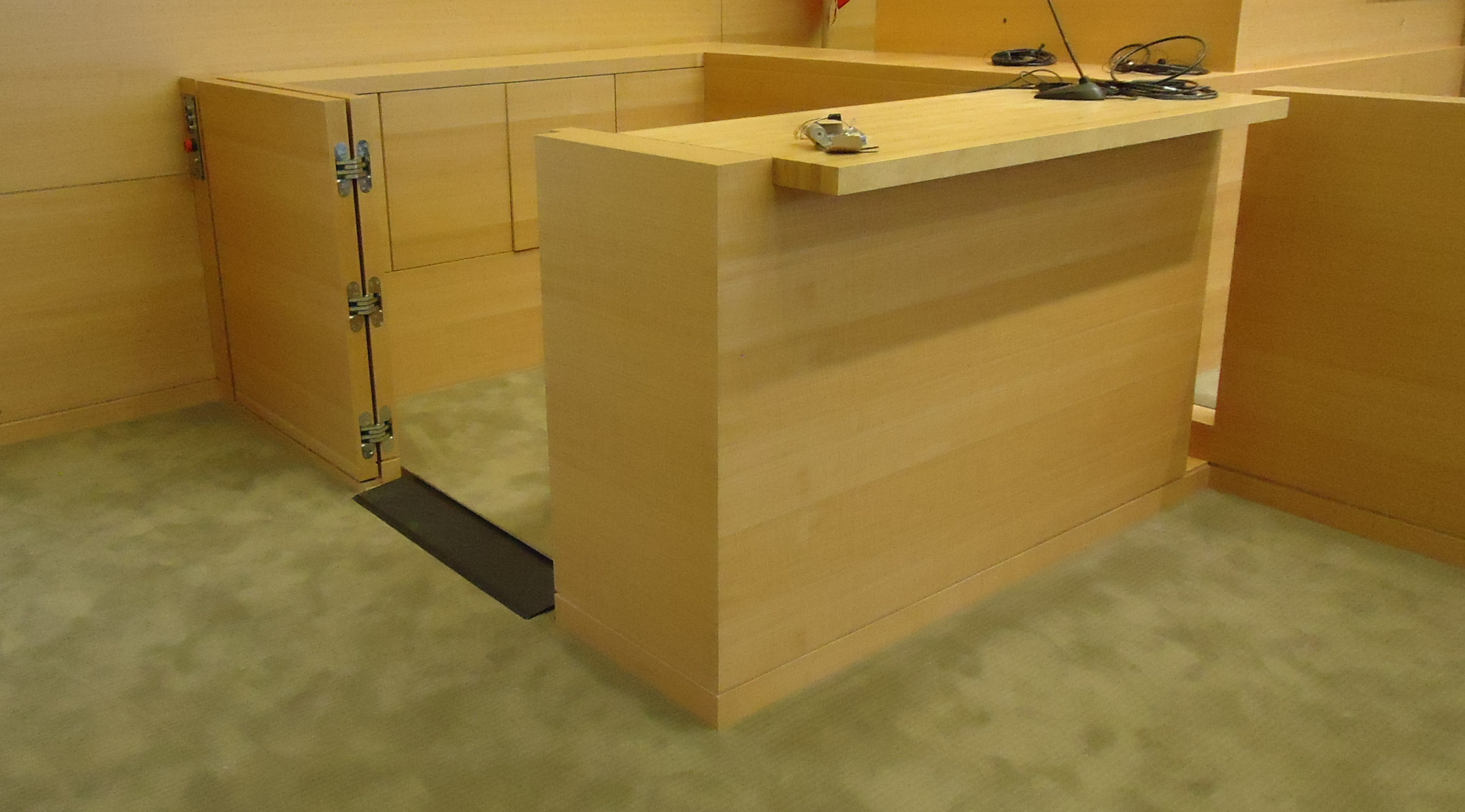 Witness lift positioned at lower level with lower level door opened. Equipped with threshold ramp to allow wheelchair access. Lift encased in wood millwork blending in with courtroom millwork. Lift is readily available and independently operable.