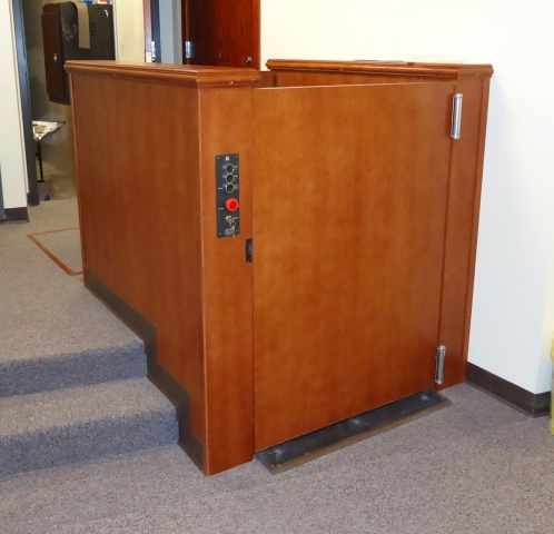 Lift door at lower level is closed. Lift in church provides access to and from the chancel. Lift is positioned next to stairs and is encased in wood millwork blending in with surrounding aesthetics. Lift function readily available, independently operable.