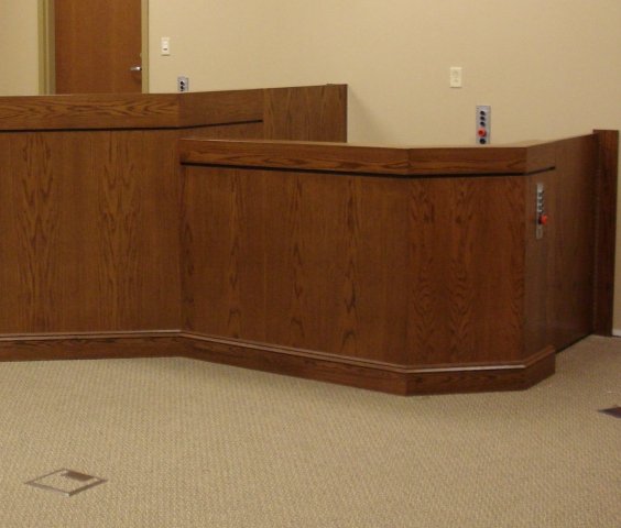 Lift positioned at witness or intermediate level and the lower level door and the door to the judge bench are closed. Lift encased in wood millwork blending in with courtroom millwork. Lift is readily available and independently operable.