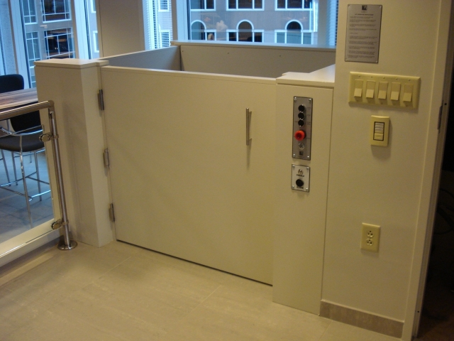 Close-up view from upper level approach to the lift with the upper level door closed. Lift ready to receive passenger to run lift to the lower level. Lift encased in wood painted white to blend in with surrounding aesthetics. Lift function readily available, independently operable.