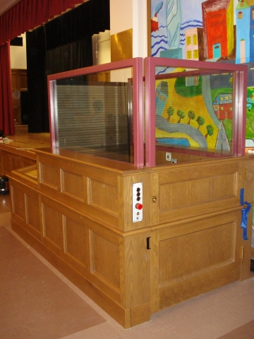 Lower level door closed, upper level guarded by roll-up barrier. Lift in school providing access to a stage in multipurpose room. Lower half of lift encased in wood millwork. Upper half of lift stationary sidewalls made of glass allowing mural to be visible from seating area. Lift function readily available, independently operable.