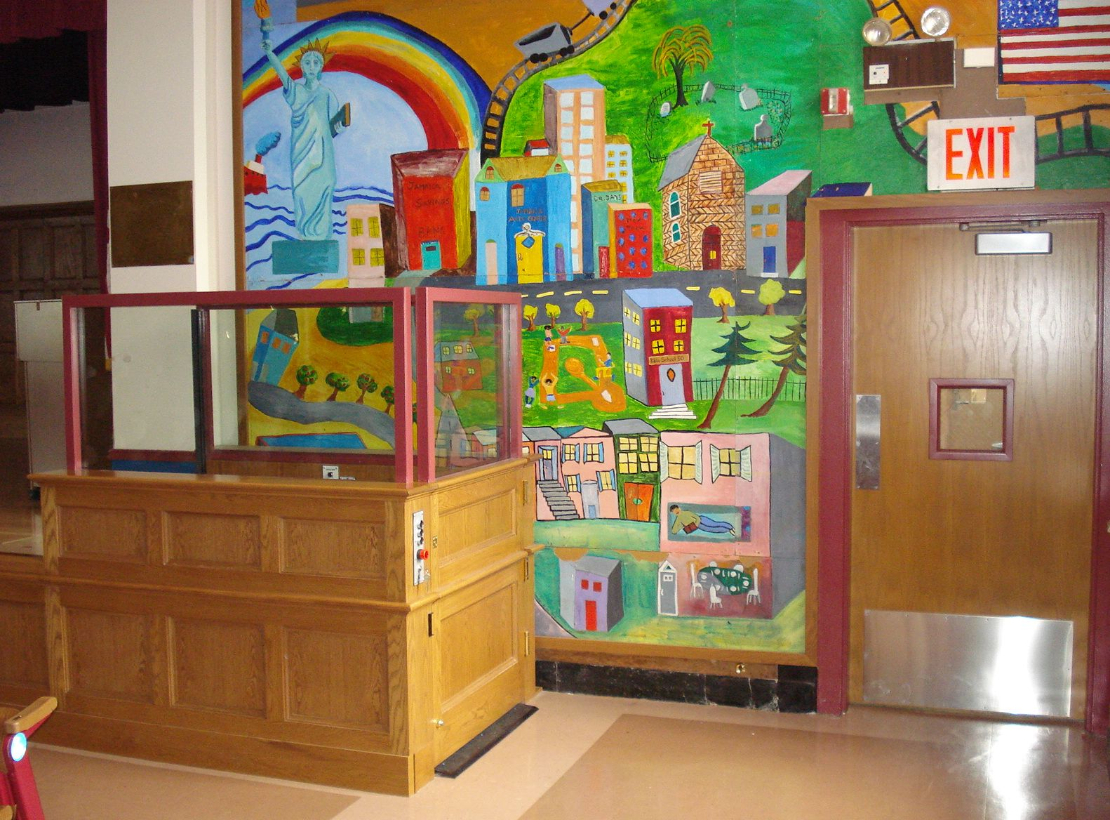 Side view of lift in school providing access to a stage in multipurpose room. Lower half of lift encased in wood millwork. Upper half of lift stationary sidewalls made of glass allowing mural to be visible from seating area. Lift function readily available, independently operable.