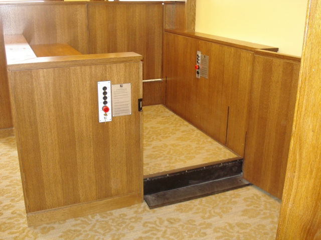 Lift positioned at witness or intermediate level allowing ambulatory access to the witness stand and the judge's bench. The lower level door is opened and the door to the judge's bench is closed. Equipped with threshold ramp to allow wheelchair access when the lift is at the lower level. Lift encased in wood millwork blending in with courtroom millwork. Lift is readily available and independently operable.