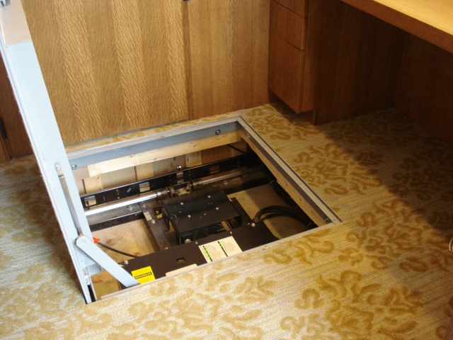 Close-up view of access hatch at the upper level. Hatch is opened, providing access to lift motor and control cabinet.