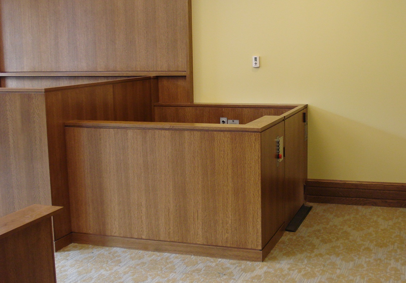 Lift positioned at witness level with lower level door closed. Equipped with threshold ramp to allow wheelchair access when the lift is at the lower level. Lift encased in wood millwork blending in with courtroom millwork. Lift is readily available and independently operable.