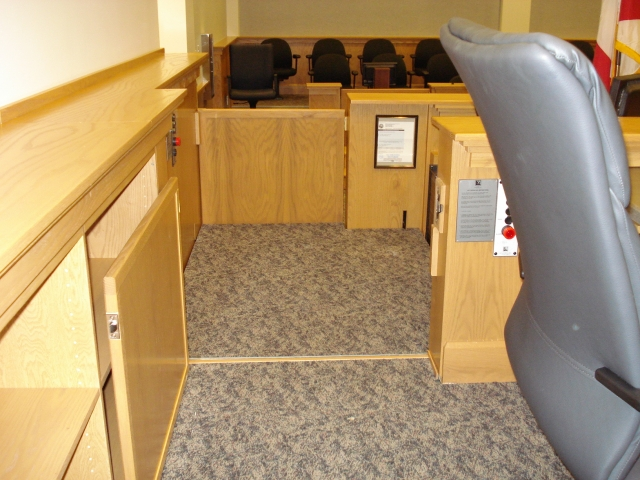 View of the lift from the judge's bench. Lift positioned at the judge's bench or upper level with upper level door opened and the lower level door closed. Lift encased in wood millwork blending in with courtroom millwork. Lift is readily available and independently operable.