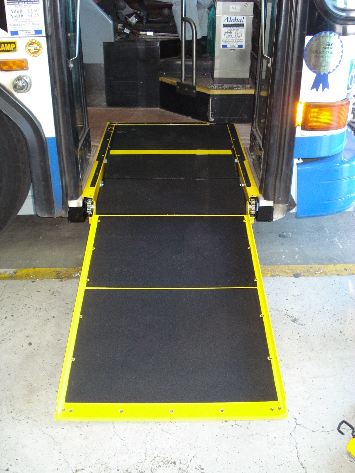 New ramp deployed to ground to allow wheelchair access to the bus.