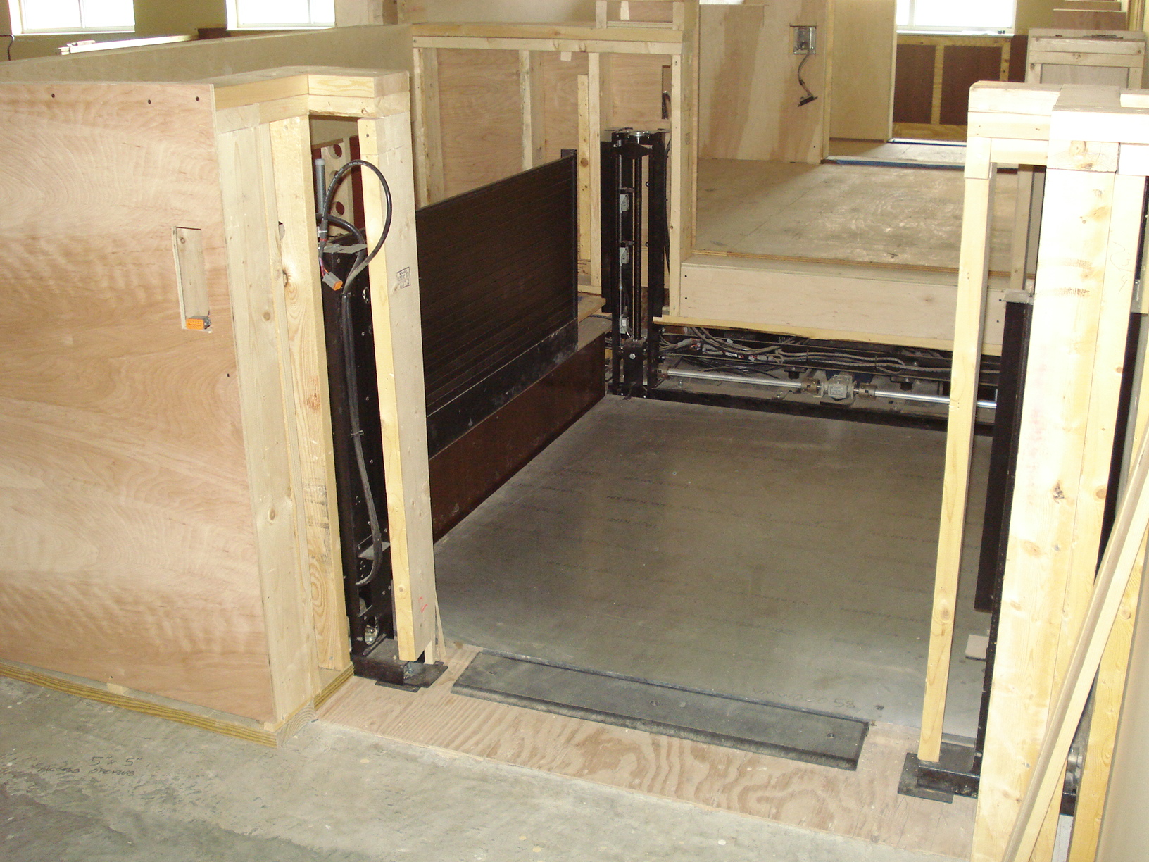 Courtroom under construction. Lift is installed and framing around lift mechanism is partially completed.