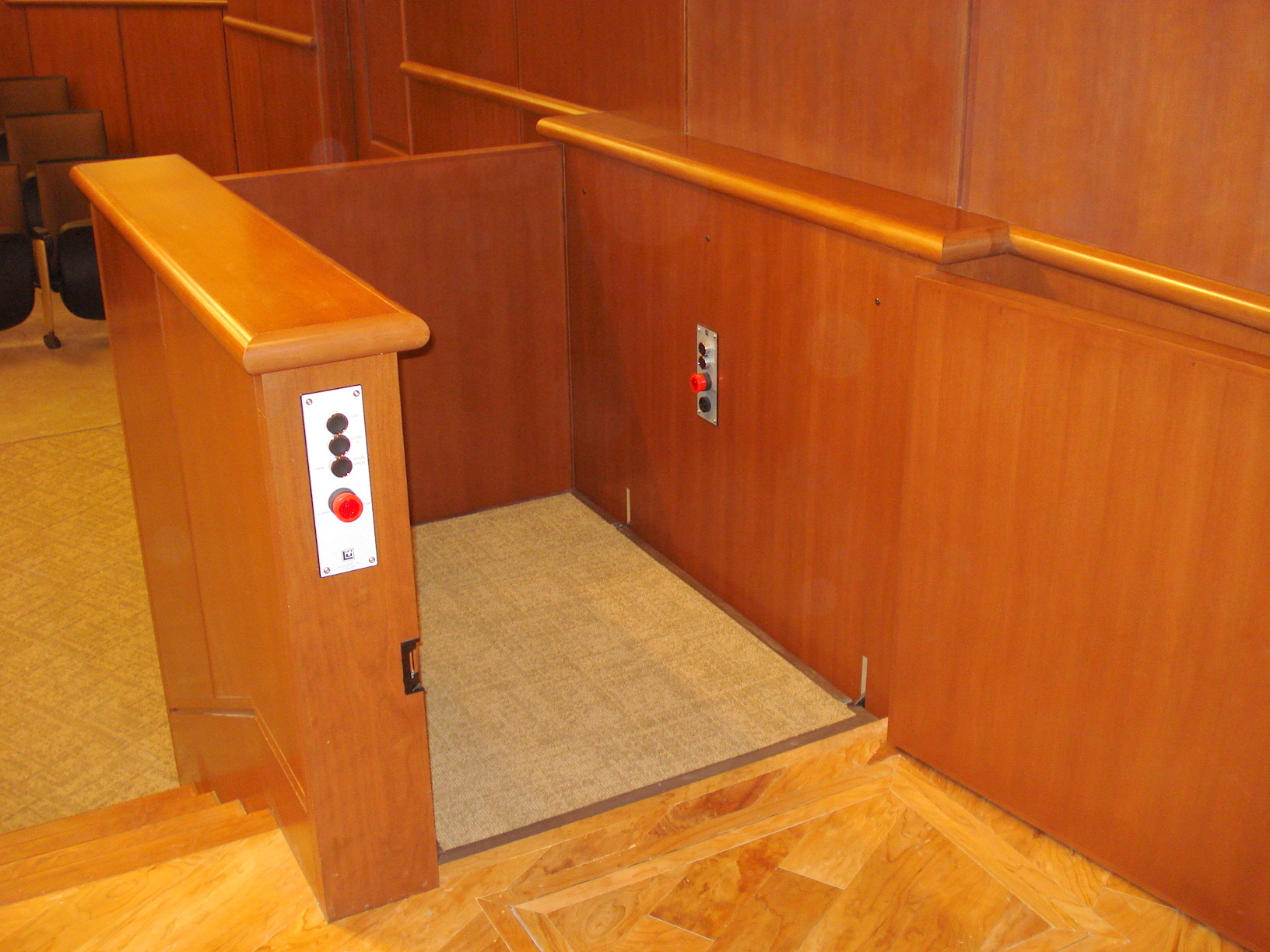 Lift door at upper level is opened. Lift in auditorium provides access to and from the stage. Lift is positioned next to stairs and is encased in wood millwork blending in with surrounding aesthetics. Lift function readily available, independently operable.