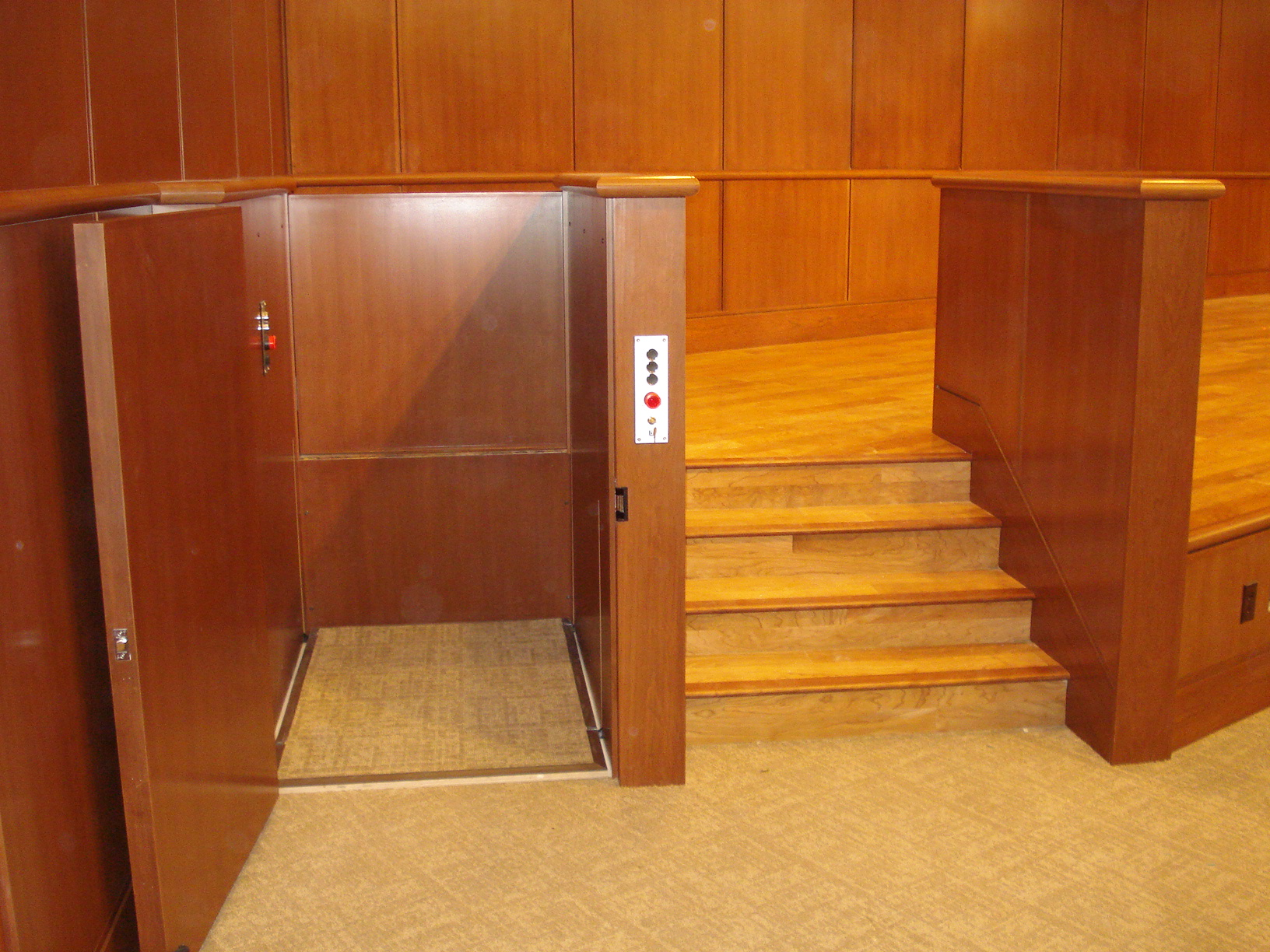 Lift door at lower level is opened. Lift in auditorium provides access to and from the stage. Lift is positioned next to stairs and is encased in wood millwork blending in with surrounding aesthetics. Lift function readily available, independently operable.