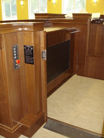 Lift positioned at lower level with lower level door opened and the door to the judge's bench closed. Equipped with threshold ramp to allow wheelchair access. Lift encased in wood millwork blending in with courtroom millwork. Lift is readily available and independently operable.