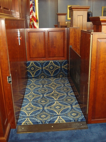 Lift positioned at lower level with lower level door opened and the door to the judge's bench closed. Roll-up barrier in the up postion to guard the desk area of the witness stand during lift operation.Equipped with threshold ramp to allow wheelchair access. Lift encased in wood millwork blending in with courtroom millwork. Lift is readily available and independently operable.