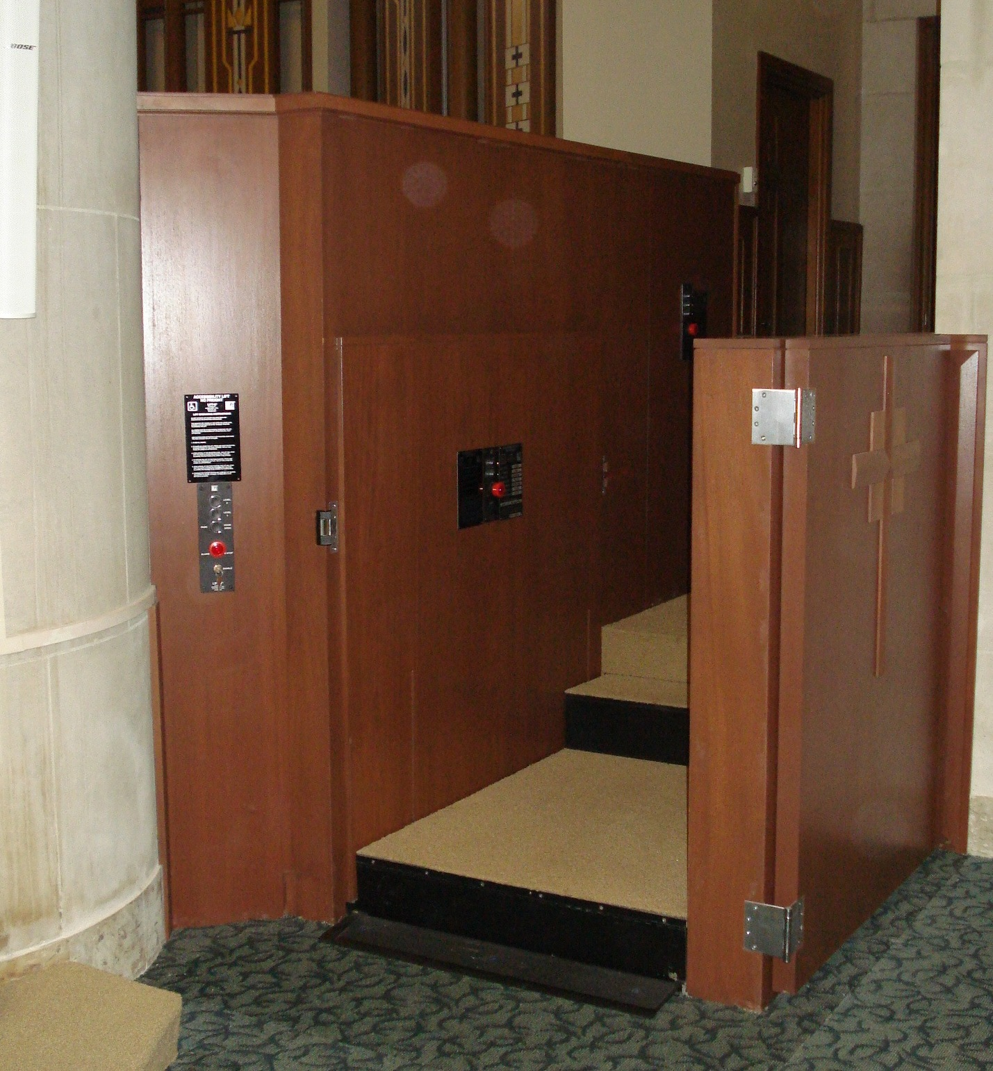 Both doors are opened. Lift in church utilizes retractable step to allow ambulatory access to and from the chancel. Lift encased in wood millwork blending in with surrounding aesthetics. Lift function readily available, independently operable.