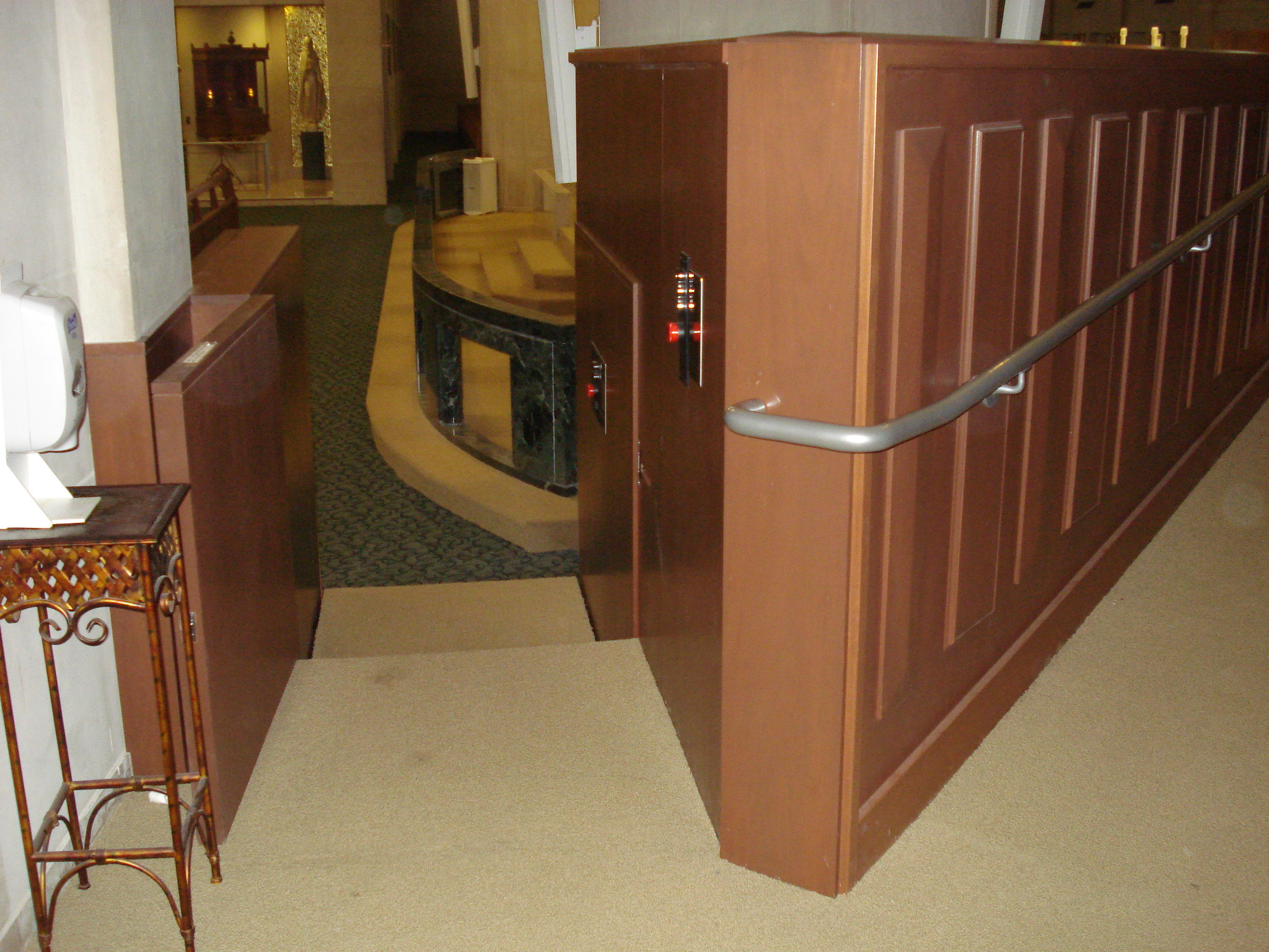 Both doors are opened, view from upper level. Lift in church utilizes retractable step to allow ambulatory access to an from the chancel. Lift encased in wood millwork blending in with surrounding aesthetics. Lift function readily available, independently operable.