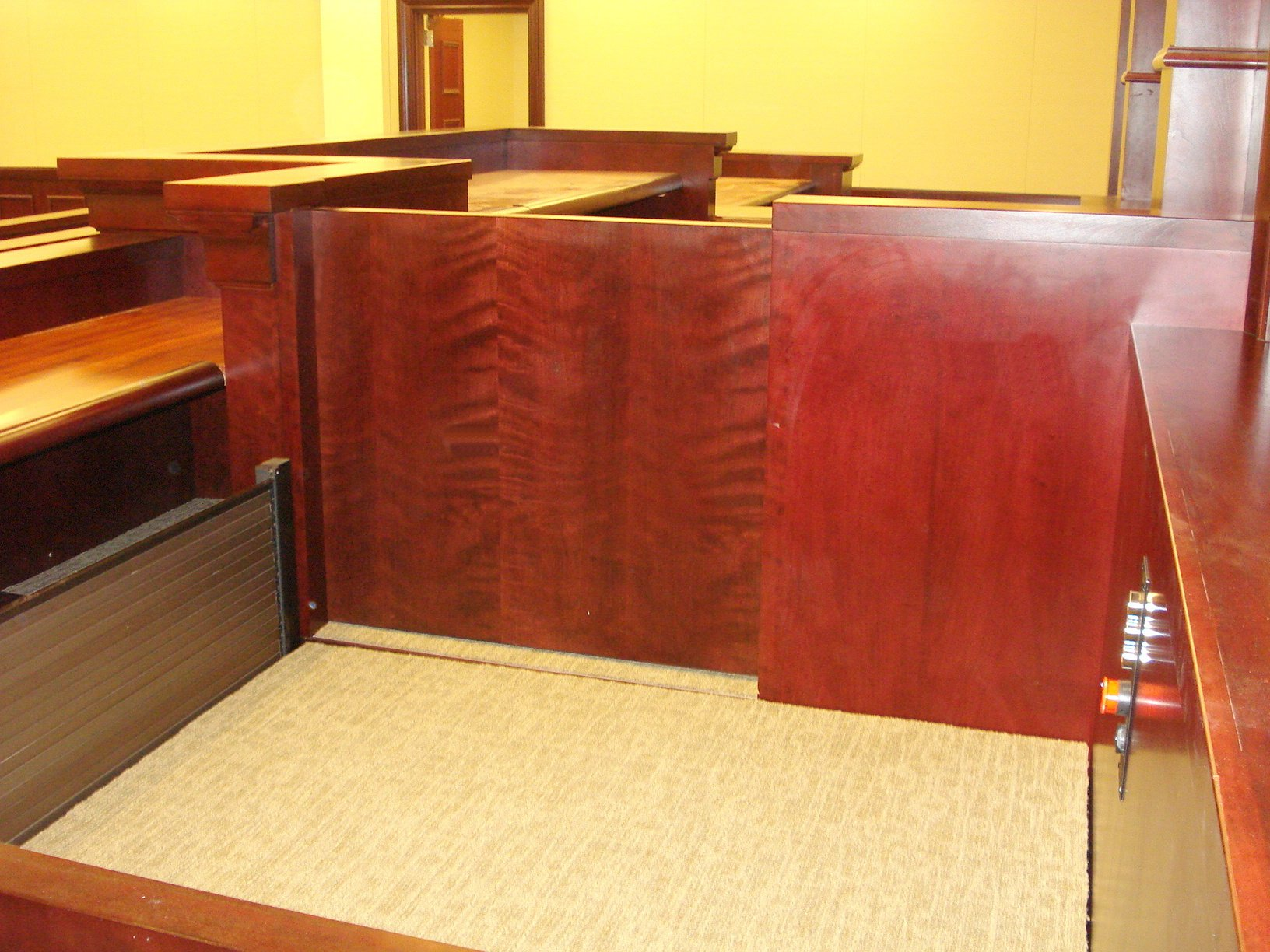 View of the lift from the side of the witness stand. Lift positioned at witness or intermediate level, both doors are closed and the roll-up barrier is up to guard the desk area during lift operation. Lift encased in wood millwork blending in with courtroom millwork. Lift is readily available and independently operable.
