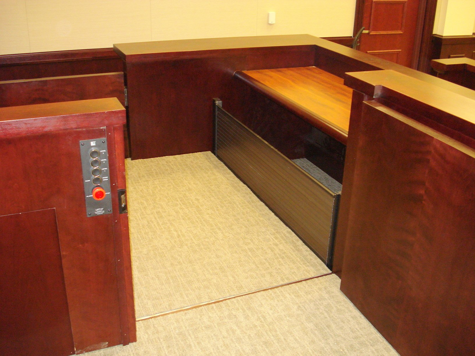 View of the lift from the judge bench. Lift positioned at the upper level with upper level door opened and the lower level door closed. Lift encased in wood millwork blending in with courtroom millwork. Lift is readily available and independently operable.