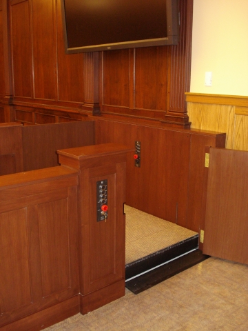 Lift positioned at witness level with lower level door opened. Equipped with threshold ramp to allow wheelchair access when the lift is at the lower level. Lift encased in wood millwork blending in with courtroom millwork. Lift is readily available and independently operable.