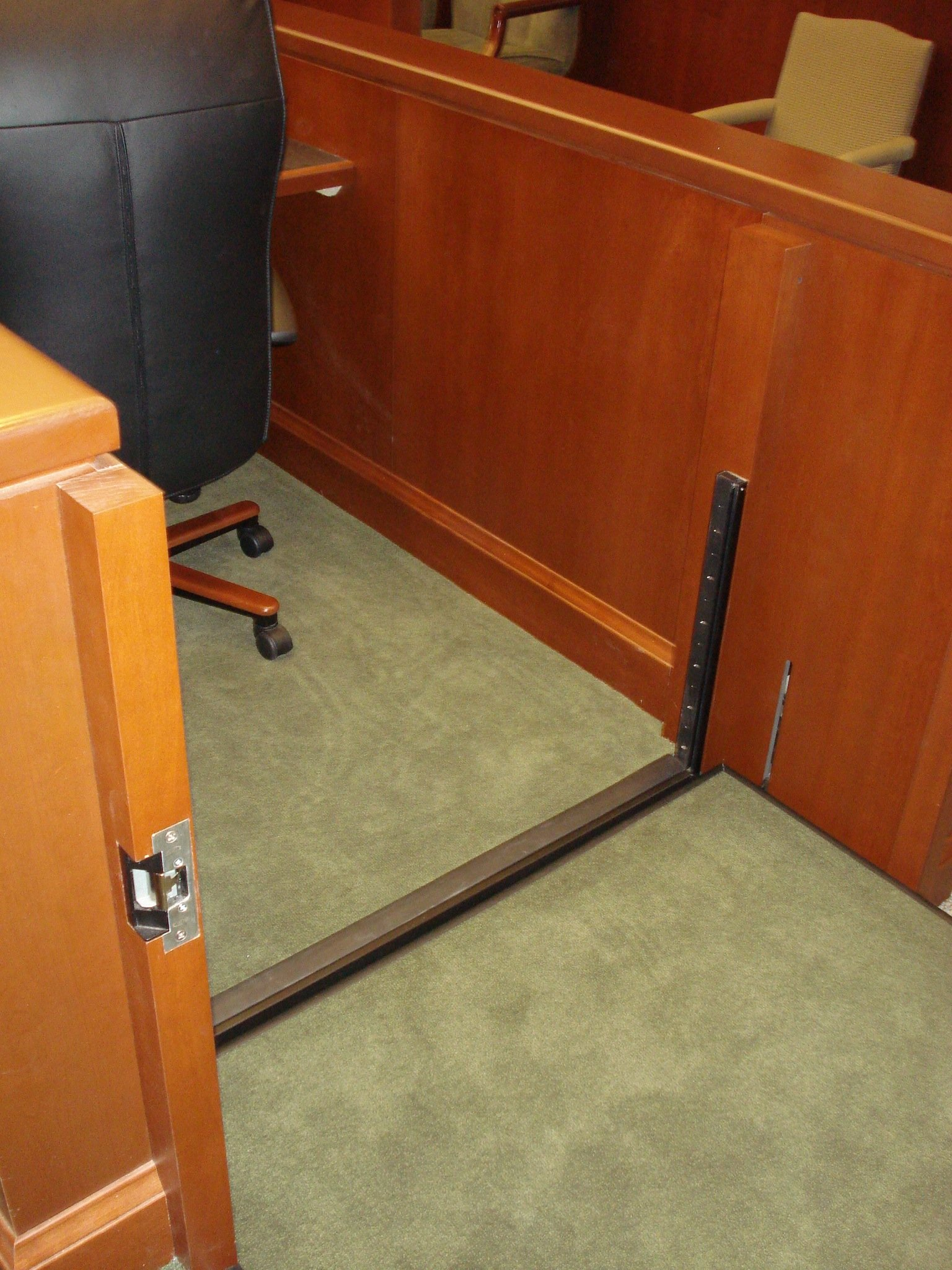 View from inside the lift with the lift positioned at the witnes level.  The roll-up barrier is down making the desk and chair accessible.