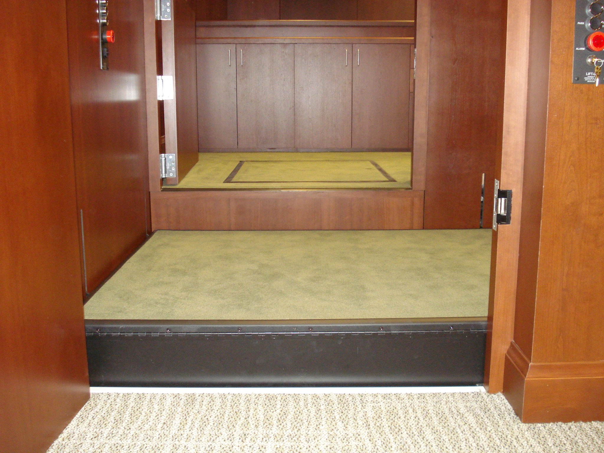 Ground level view of the lift platform at the witness or intermediate level Both doors are openened allowing ambulatory access to the witness stand and judge's bench. Lift is readily available and independently operable.
