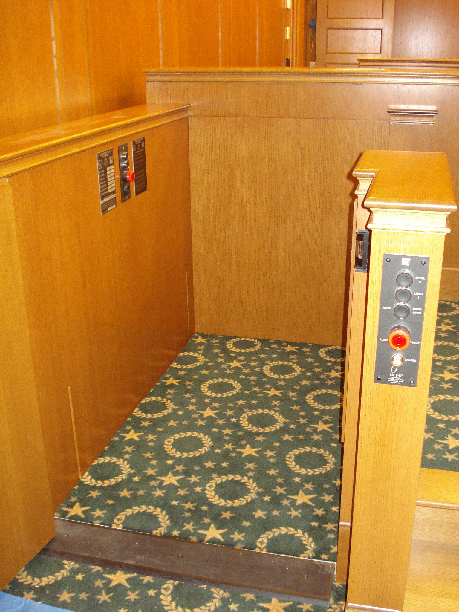 Lift positioned at lower level with lower level door opened. Equipped with threshold ramp to allow wheelchair access when the lift is at the lower level. Lift encased in wood millwork blending in with courtroom millwork. Lift is readily available and independently operable.