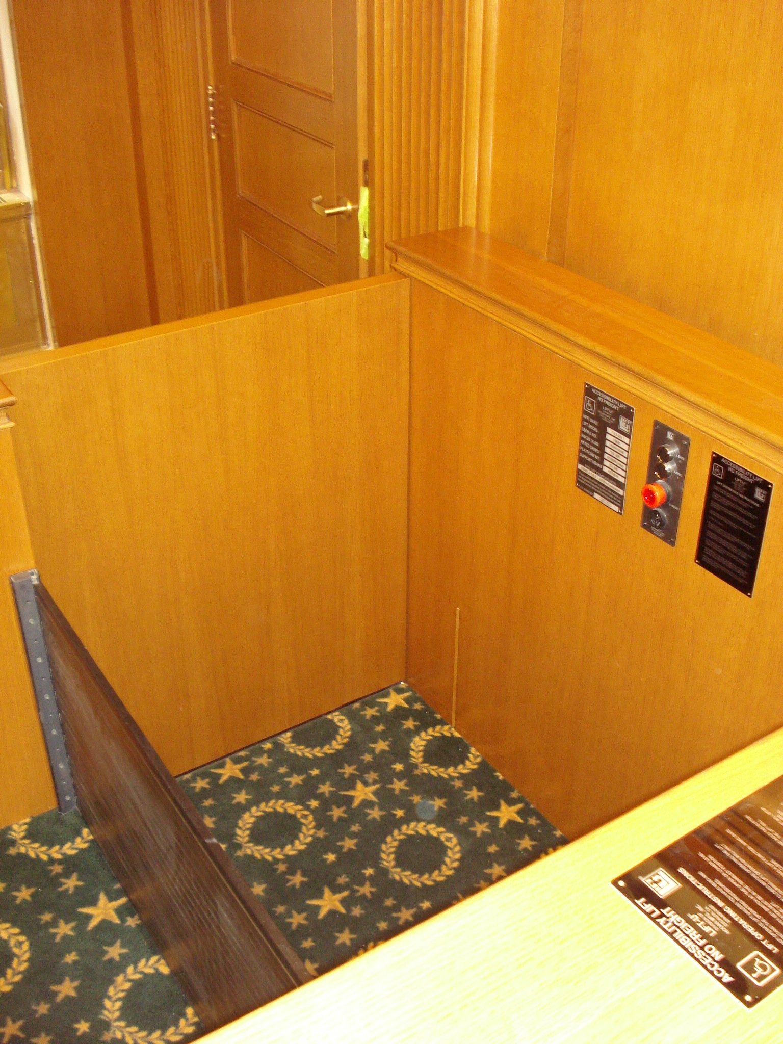 View from Judge's bench looking down into lift. Lift positioned at lower level with lower level door closed and the roll-up barrier up to guard the desk area in the witness stand. Lift encased in wood millwork blending in with courtroom millwork. Lift is readily available and independently operable.