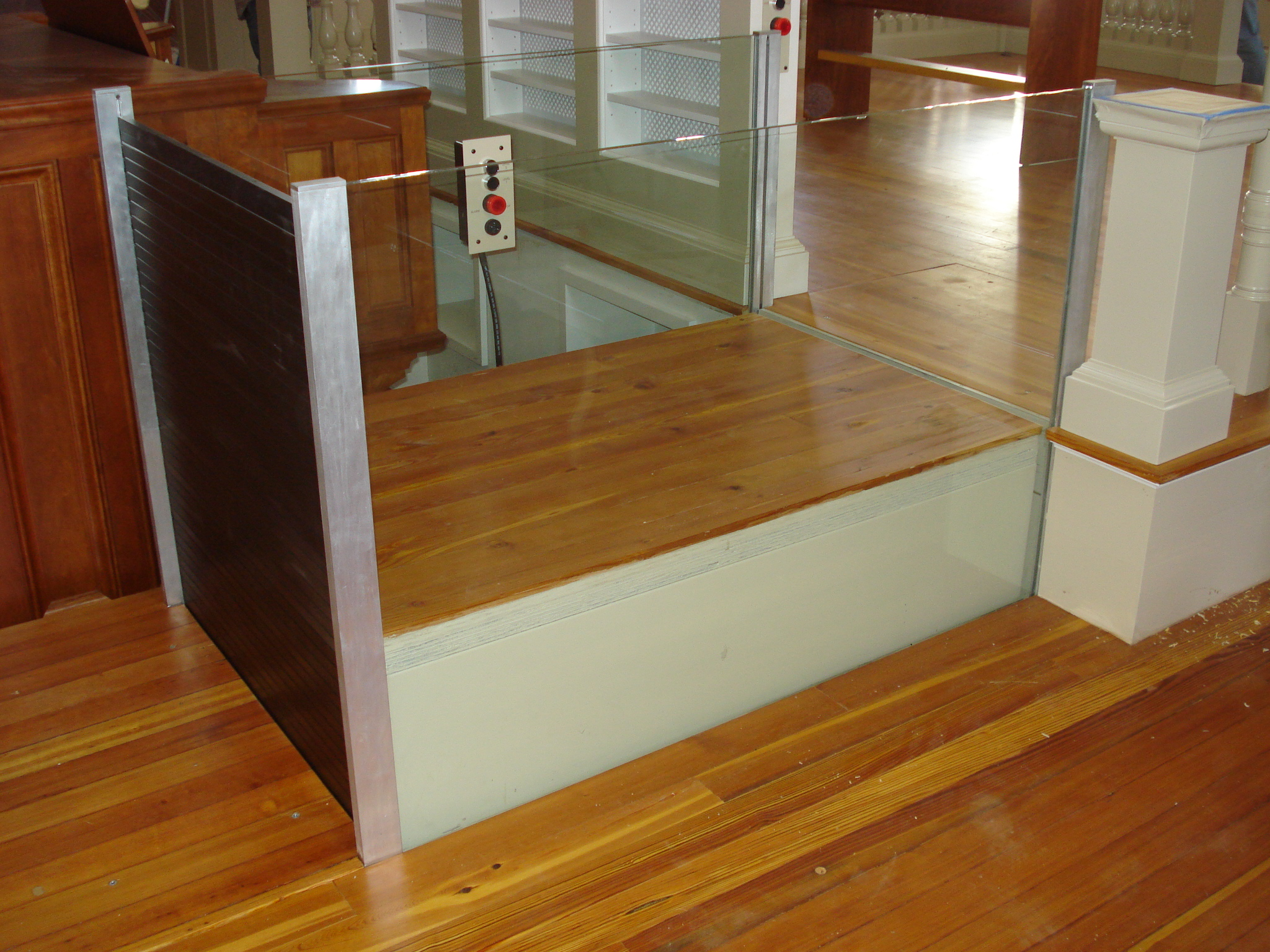 Side view of the lift in a church application with the lower level roll-up barrier in the  up position and the upper level barrier is in the down position, The lift is ready to receiva a passenger to run the lift down to access the lower level where the organ is located. Lift utilizes glass stationary sidewalls to blend in with surrounding aesthetics.