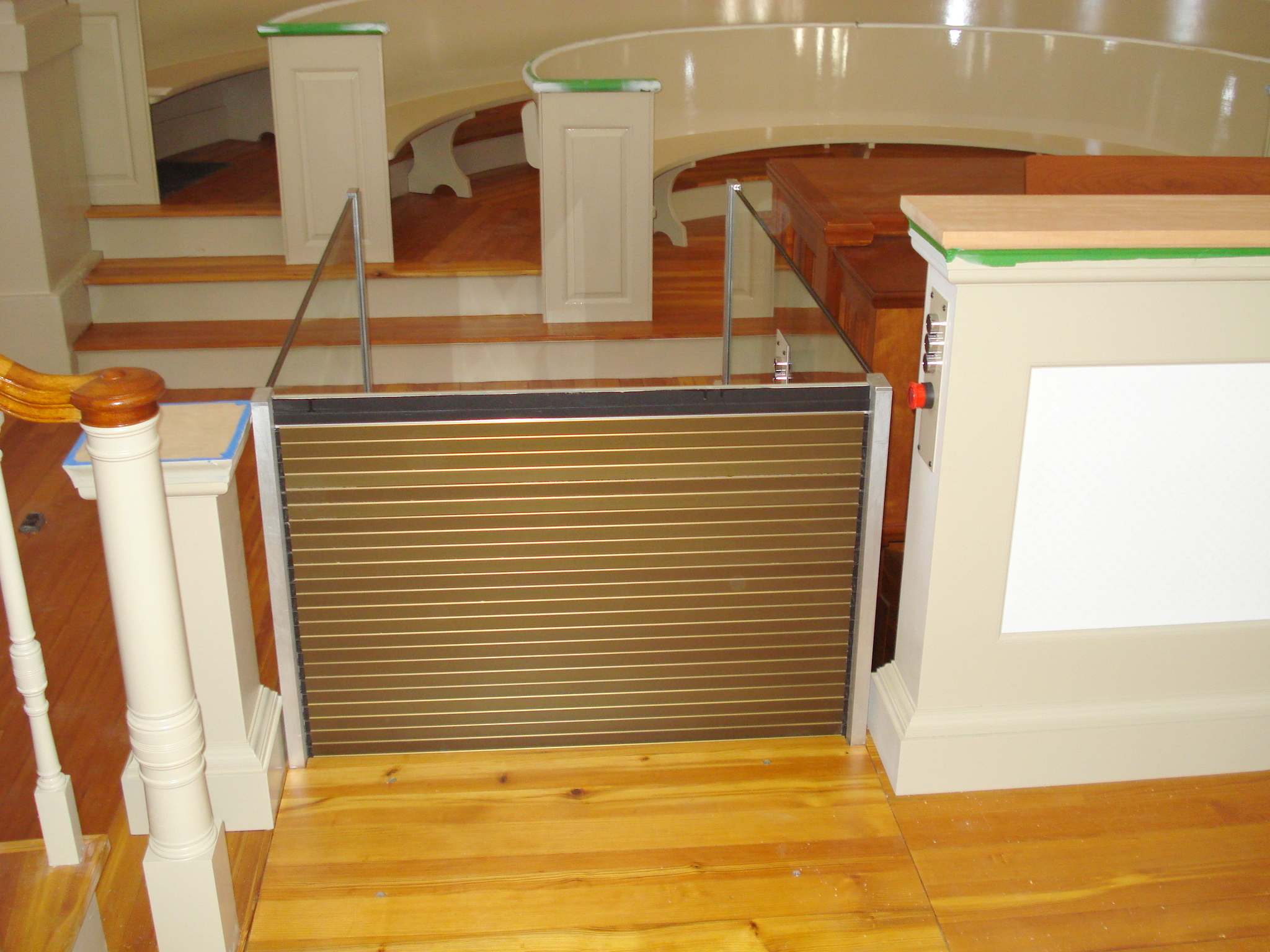 View of the lift in a church application from the upper level approach with the upper level roll-up barrier in the up position. Lift utilizes glass stationary sidewalls to blend in with surrounding aesthetics. Lift function readily available, independently operable.