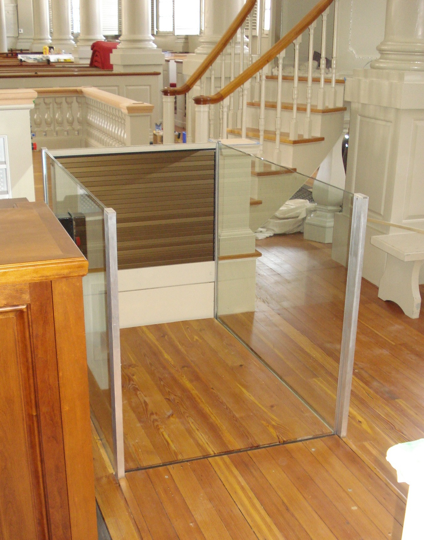 Lift in a church application at the lower level ready to receive a passenger to run the lift to the upper level.  The upper level roll-up barrier is in the up popsition to guard the upper level. Lift utilizes glass stationary sidewalls to blend in with surrounding aesthetics.