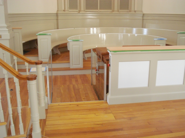 Upper level approach of the lift in a church application with roll-up barriers positioned under the floor allowing ambulatory access to and from the organ. Lift utilizes glass stationary sidewalls to blend in with surrounding aesthetics. Lift function readily available, independently operable.