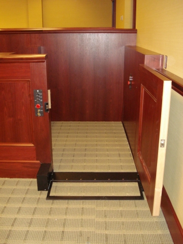 Lift positioned at lower level with lower level door opened. The operable step is in the ramp position to allow wheelchair access. Lift encased in wood millwork blending in with courtroom millwork. Lift is readily available and independently operable.