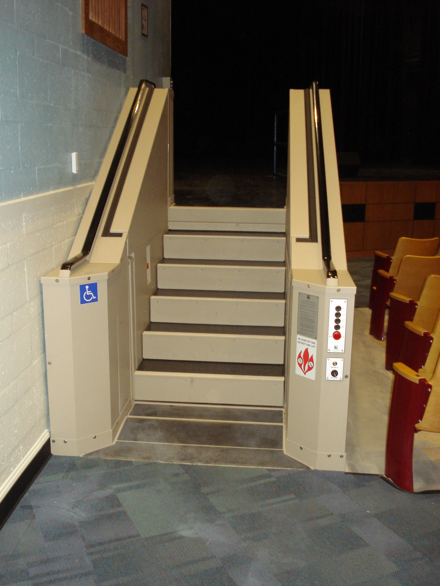 Tan in color. In step position for ambulatory access to stage in auditorium. Lift function readily available, independently operable.