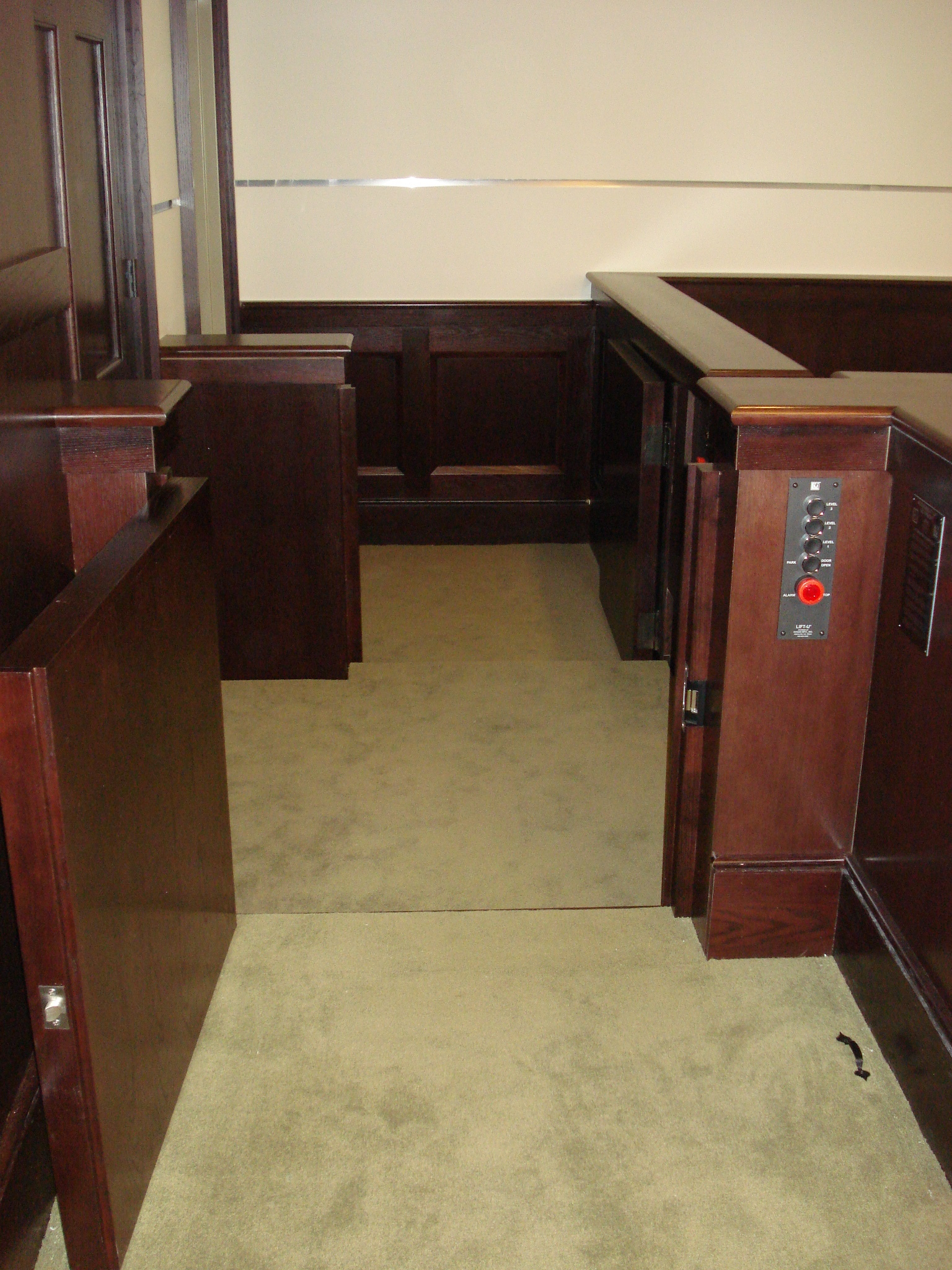 View of the lift from the judge's bench. Lift positioned at the witness or intermediate level with both doors opened. Lift encased in wood millwork blending in with courtroom millwork. Lift is readily available and independently operable.