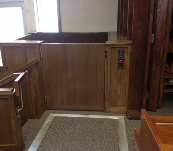 Lift doors are closed, view from upper level. Lift in church provides access to an from the chancel. Lift encased in wood millwork blending in with surrounding aesthetics. Lift function readily available, independently operable.
