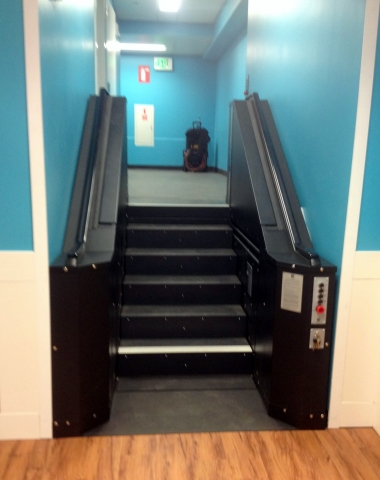 Black in color. In step position for ambulatory access to employee break room. Lift function readily available, independently operable.