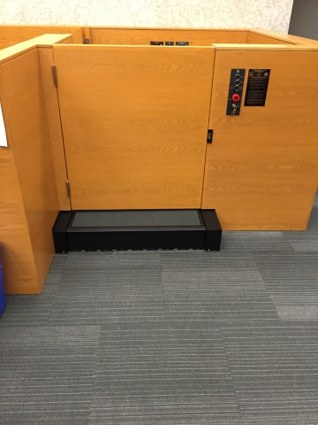 Lift positioned at witness level with lower level door closed. Equipped with operable step to allow ambulatory access. Lift encased in wood millwork blending in with courtroom millwork. Lift is readily available and independently operable