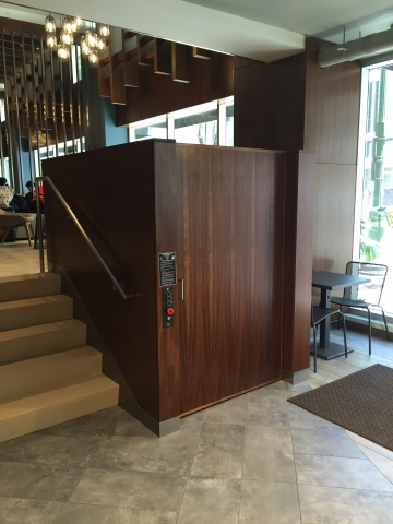 Lift doors closed. Lift encased in wood millwork blending in with surrounding aesthetics. Lift function readily available, independently operable.
