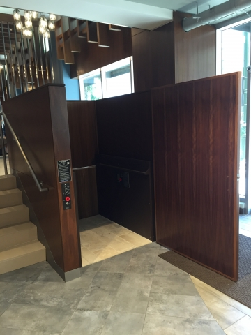 Lower level door opened, lift ready to receive passenger to run lift to the upper level. Lift encased in wood millwork blending in with surrounding aesthetics. Lift function readily available, independently operable.
