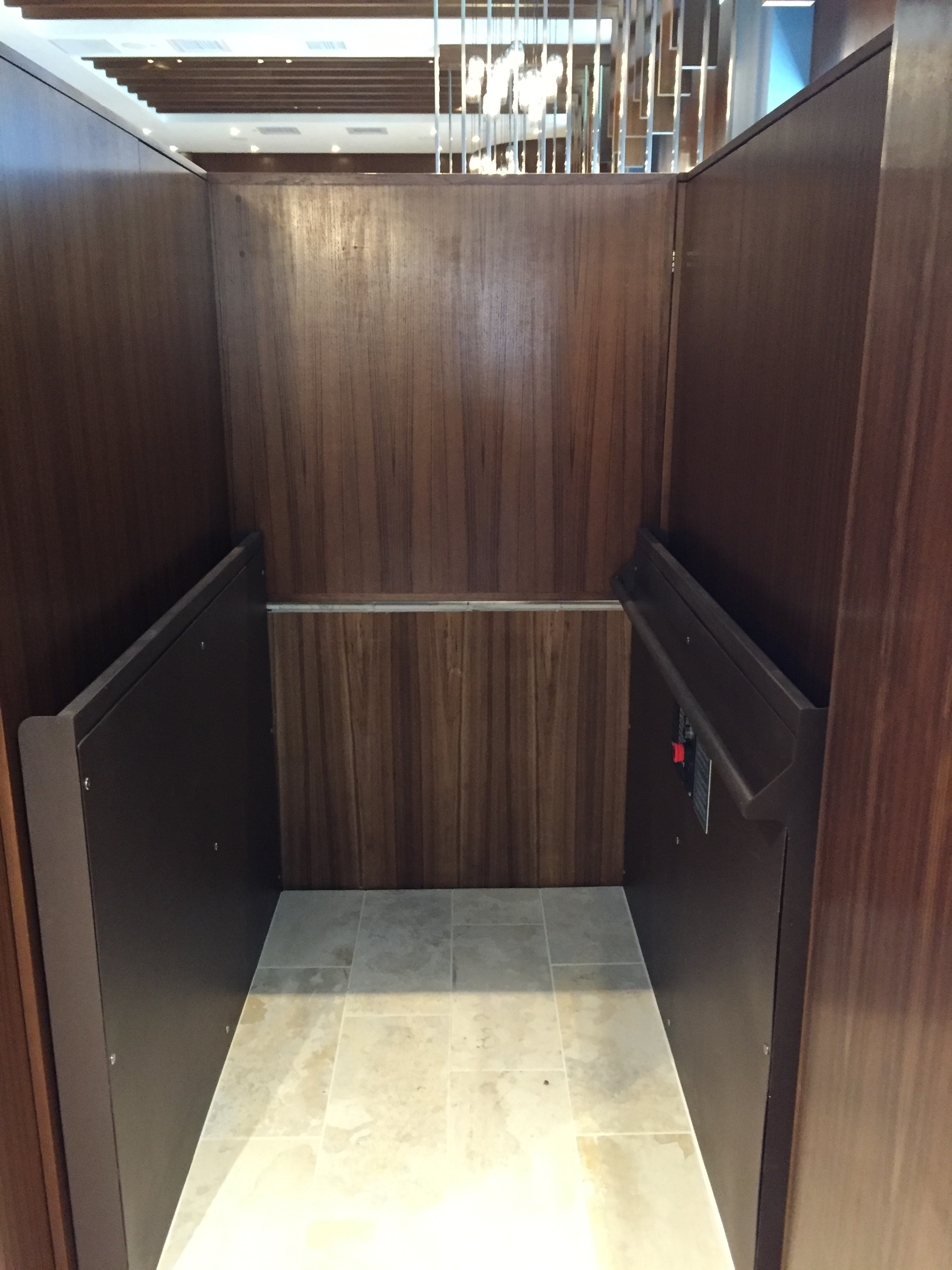 Lower level door opened. Close-up view of lift platform from lower level approach. Lift encased in wood millwork blending in with surrounding aesthetics. Lift function readily available, independently operable.